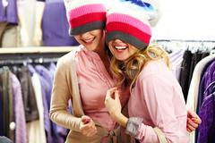 Portrait of two joyful girls with knitted caps on heads laughing in clothing dep Stock Photos