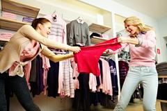 image of two greedy girls fighting for red tanktop in department store - stock photo