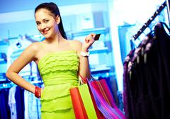 Portrait of pretty woman with paperbags and plastic card looking at camera in cl Stock Photos