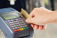 Close-up of payment machine buttons with human hand holding plastic card near by Stock Photos
