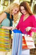 two young girls showing purchases to each other - stock photo