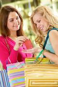 a young woman giving a little present to her girlfriend - stock photo