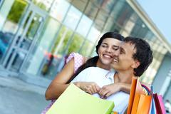 Young girl embracing her boyfriend with shopping bags Stock Photos