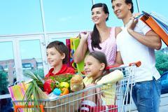 Couple with shopping bags pushing cart with two children Stock Photos