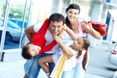 Portrait of happy family of four with shopping bags Stock Photos