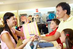 man with two children paying for purchases - stock photo