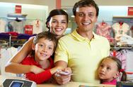 Portrait of family of four giving credit card Stock Photos