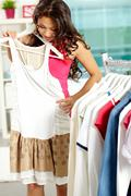 portrait of pretty woman trying on new dress in clothing department - stock photo