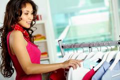 portrait of happy woman looking through new collection in clothing department - stock photo