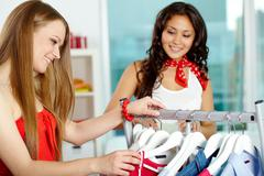 portrait of happy girls looking through new collection in clothing department - stock photo