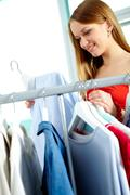 portrait of charming girl looking at shirt in clothing department - stock photo