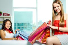 portrait of happy blonde and brunette with bags looking at camera after shopping - stock photo