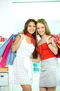 portrait of two gorgeous girls with paperbags looking at camera - stock photo