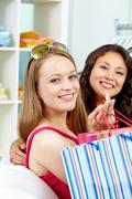 portrait of happy shoppers looking at camera with smiles after shopping - stock photo