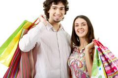 portrait of happy couple holding bags in hands - stock photo