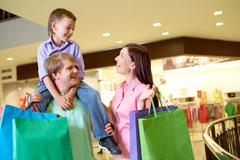 portrait of joyful woman looking at her son on father's shoulders in the mall - stock photo