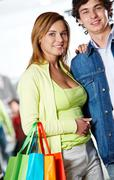Stock Photo of portrait of amorous couple looking at camera with smiles after great shopping