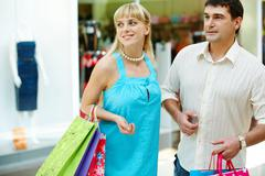 Handsome man with paperbags and his girlfriend in shopping mall Stock Photos