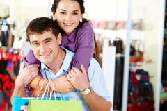 pretty woman embracing happy man in the department store - stock photo