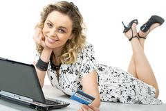 Photo of happy female with card in hand and laptop near by Stock Photos
