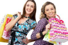 Muotokuva iloinen tyttöjen kuljettaa ostoskasseja ja katsot kameraan Kuvituskuvat