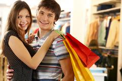 portrait of joyful husband and wife after shopping looking at camera - stock photo