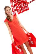 Young shopper carrying bags and looking at hangers with discount symbols Stock Photos