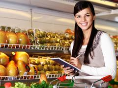Image of pretty woman looking at camera while choosing products in supermarket Stock Photos