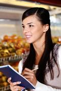 Image of pretty woman with notepad looking somewhere in supermarket Stock Photos