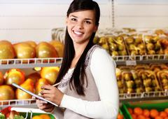 Image of pretty woman looking at camera in supermarket Stock Photos