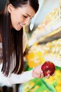 Image of happy woman with fresh apple in hand looking at it in supermarket Stock Photos
