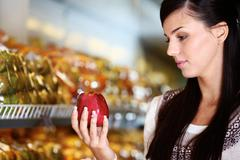 Image of young woman with fresh apple in hand looking at it in supermarket Stock Photos