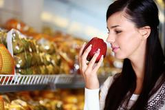 Image of young woman with fresh apple in hand smelling it in supermarket Stock Photos