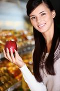 Image of happy woman with fresh apple in hand looking at camera in supermarket Stock Photos