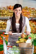 image of pretty woman with cart looking at camera - stock photo
