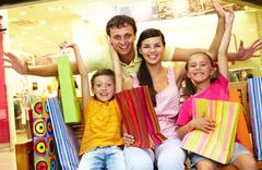 portrait of joyful family sitting in store with plenty of shopping bags - stock photo