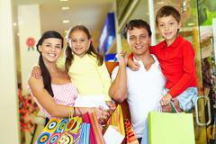 Portrait of happy parents and children with paperbags after shopping Stock Photos