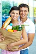 Portrait of a happy couple with foodstuff Stock Photos