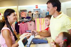Man with two children paying for purchases Stock Photos