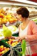 Image of senior woman choosing products in supermarket with cart near by Stock Photos