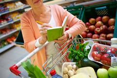Image of senior woman looking at product list with goods in cart near by Stock Photos