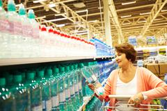 image of mature customer choosing water from big assortment in a shop - stock photo
