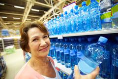 image of mature customer holds bottle of pure water - stock photo
