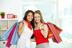portrait of happy girls with paperbags looking at camera - stock photo