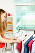 Stock Photo of portrait of charming girl choosing new dress in clothing department