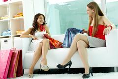 Portrait of happy girlfriends looking at each other while chatting in clothing d Stock Photos