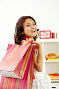 portrait of happy brunette with paperbags after shopping - stock photo