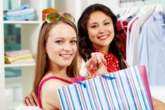 portrait of smiling shoppers looking at camera after shopping - stock photo