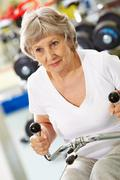 photo of active woman pumping muscles on special equipment - stock photo