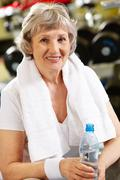 Portrait of aged woman with bottle of water in hand Stock Photos
